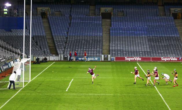 joseph-cooney-throws-a-hurl-as-richie-hogan-scores-a-goal