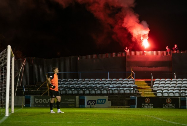 brian-murphy-watches-on-as-drogheda-fans-outside-the-fence-let-off-a-flare-to-celebrate-their-goal