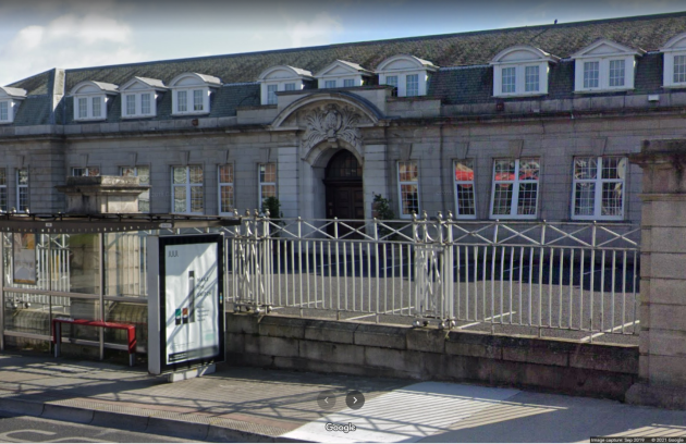 Two story building made of granite blocks with white windows and a large door surrounded by decorative stone in the middle. The windows on the second story are jutting out of the roof with a mixture of round and straight slanted roofs. There are metal railings with large piers in front of the building, with a carpark in between. A bus stop sits in front of the railings beside the road.