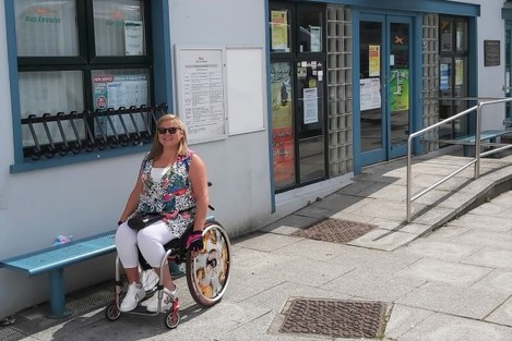 Disability activist Vicky Matthew - wheelchair user wearing sunglasses, a bright top with white trousers - outside a Bus Éireann office which has a ramp leading to its door.