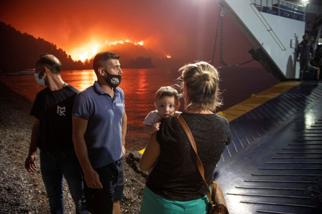 people-board-a-ferry-during-evacuation-as-a-wildfire-burns-in-the-village-of-limni-on-the-island-of-evia-greece-august-6-2021-picture-taken-august-6-2021-reutersnicolas-economou