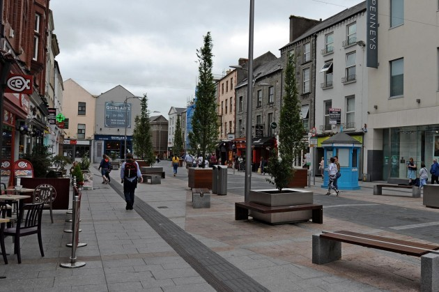 The pedestrian zone of the Mall in Tralee - a street lined with shops and cafes - which has no kerbs and is all on the same level, with some tactile paving beside a path that lies between the road section and seating areas. There are a number of planters with trees lining the road section.
