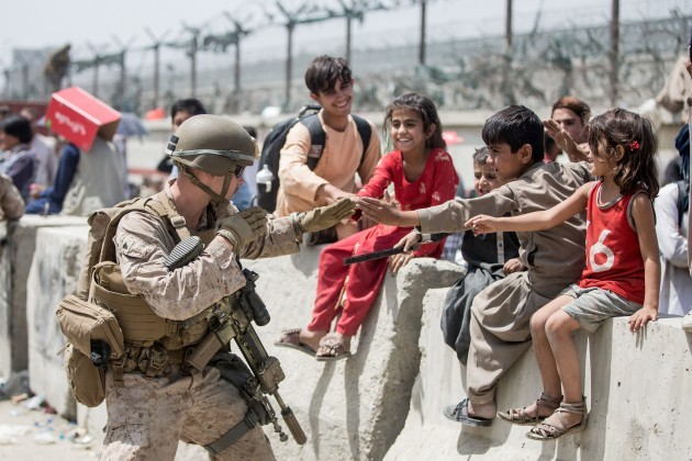 kabul-afghanistan-20th-aug-2021-a-marine-with-special-purpose-marine-air-ground-task-force-crisis-response-central-command-spmagtf-cr-cc-plays-with-children-waiting-to-process-during-an-evacuati