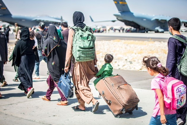 a-child-looks-at-the-aircraft-as-he-is-strolled-towards-his-flight-during-an-evacuation-at-hamid-karzai-international-airport-kabul-afghanistan-aug-24-u-s-service-members-are-assisting-the-depar