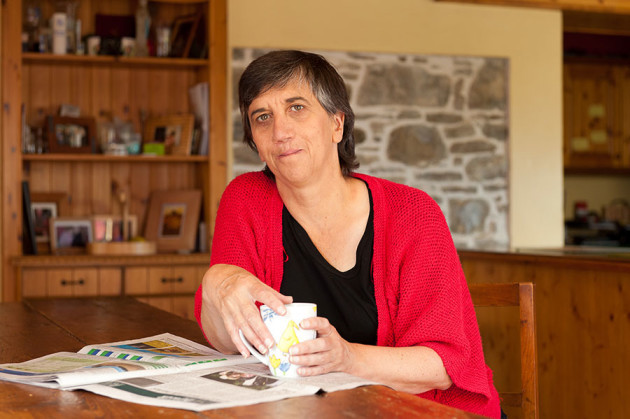 Kate Carmody wearing a black top and red cardigan sits at her kitchen table with a cup of tea in her hands.