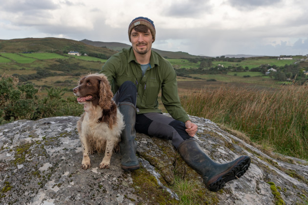 Josh Mathews in warn, winter farm clothes sitting on top of a large rock on the family farm with Moose the dog in Co Mayo